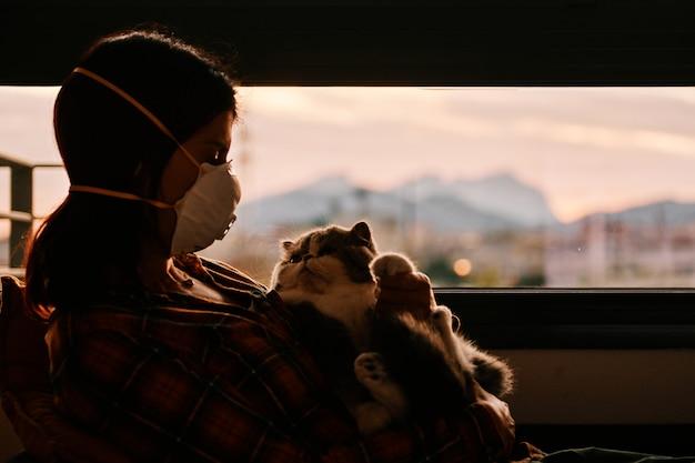 Frau mit maske und ihrer exotischen katze während der coronavirus-krise - bleiben sie zu hause konzept