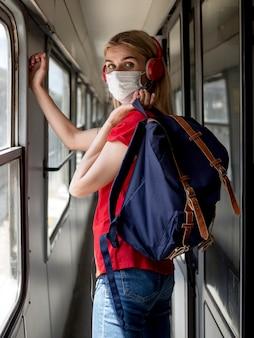 Frau mit maske und kopfhörern im zug