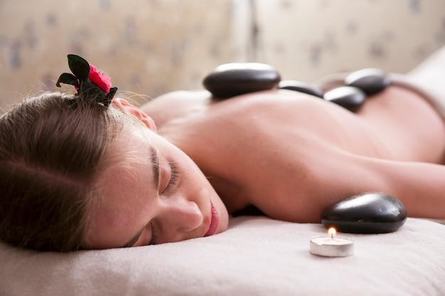 Frau mit massage-steine auf dem rücken