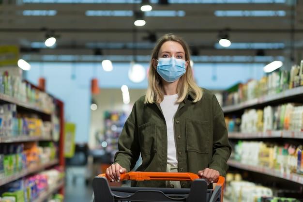 Frau mit medizinischer gesichtsmaske schiebt einkaufswagen im supermarkt. junges mädchen, das wählt, lebensmittelgeschäfte sucht, um zu kaufen. mädchen geht durch supermarkt oder laden. fröhliche hübsche frau, die im einkaufszentrum spazieren geht