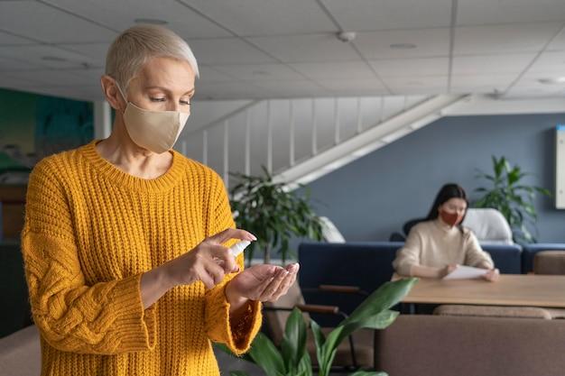 Frau mit medizinischer maske bei der arbeit