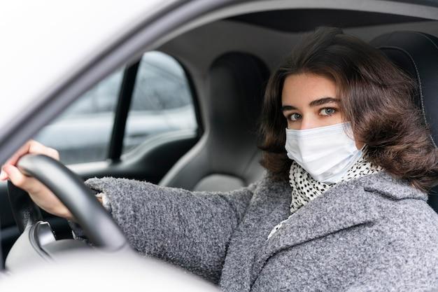 Frau mit medizinischer maske, die auto fährt