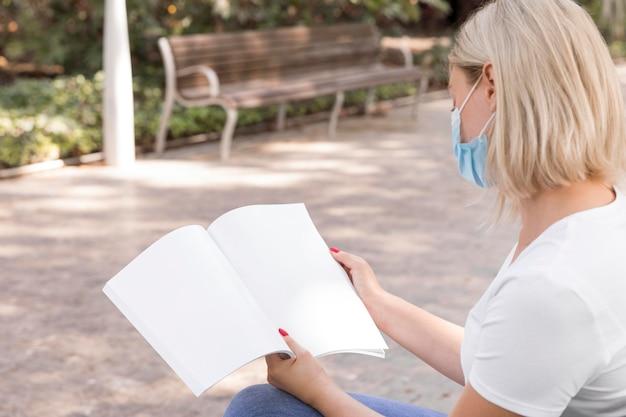 Frau mit medizinischer maske, die buch draußen liest