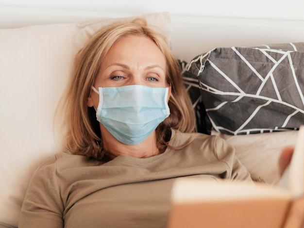 Frau mit medizinischer maske, die buch in quarantäne liest