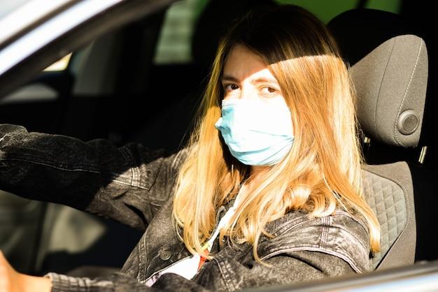 Frau mit medizinischer maske, die ein auto fährt