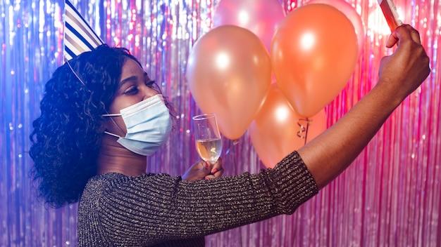 Frau mit medizinischer maske, die ein selfie nimmt