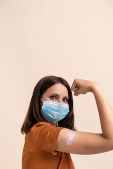 Frau mit medizinischer maske, die einen aufkleber am arm zeigt, nachdem sie einen impfstoff erhalten hat
