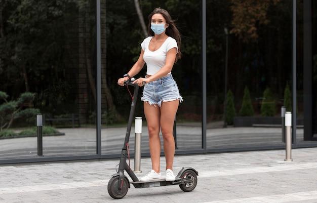 Frau mit medizinischer maske, die elektroroller reitet