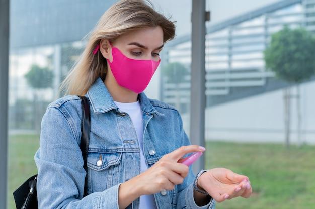 Frau mit medizinischer maske, die händedesinfektionsmittel verwendet, während sie auf den öffentlichen bus wartet