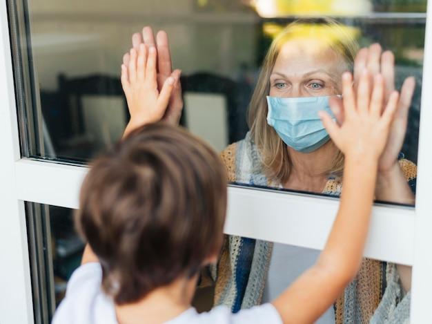 Frau mit medizinischer maske, die hallo zu neffe durch das fenster sagt