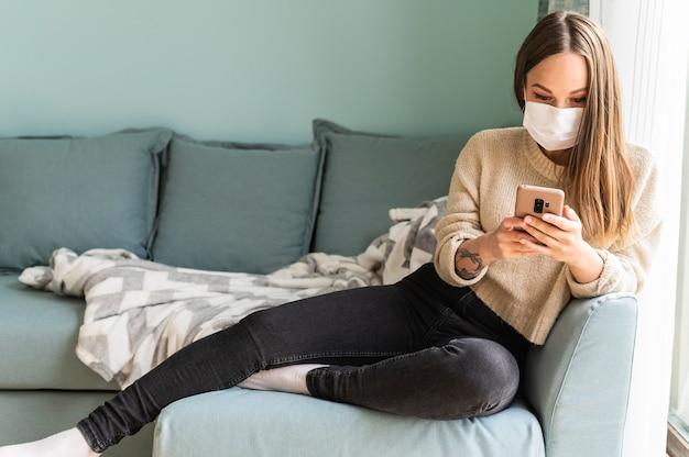 Frau mit medizinischer maske, die ihr smartphone zu hause während der pandemie verwendet