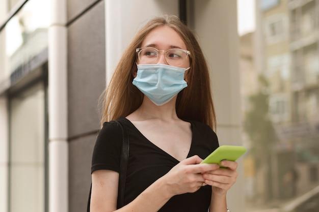 Frau mit medizinischer maske, die ihr telefon überprüft