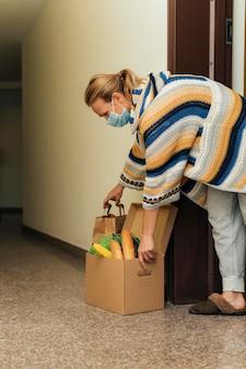 Frau mit medizinischer maske, die ihre lebensmittel in der quarantäne abholt