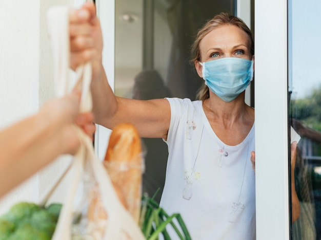 Frau mit medizinischer maske, die ihre lebensmittel in der selbstisolierung aufnimmt