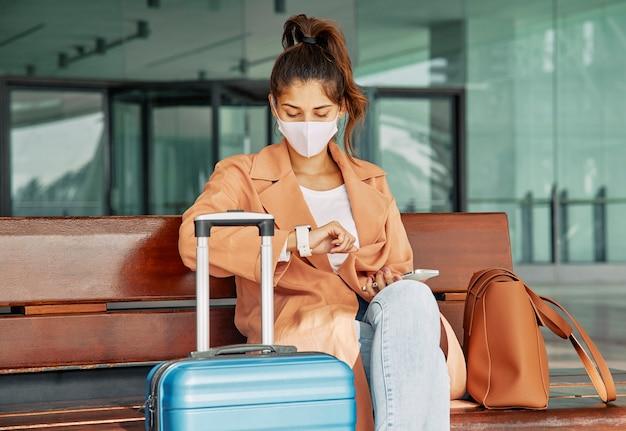 Frau mit medizinischer maske, die ihre uhr am flughafen während der pandemie betrachtet