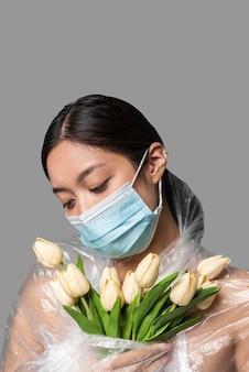 Frau mit medizinischer maske, die ihren körper mit plastik und blumen bedeckt hat