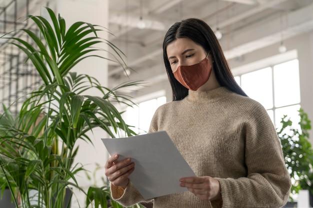 Frau mit medizinischer maske, die notizen bei der arbeit prüft