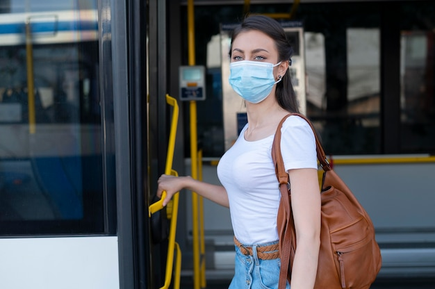 Frau mit medizinischer maske, die öffentlichen bus für den transport nutzt