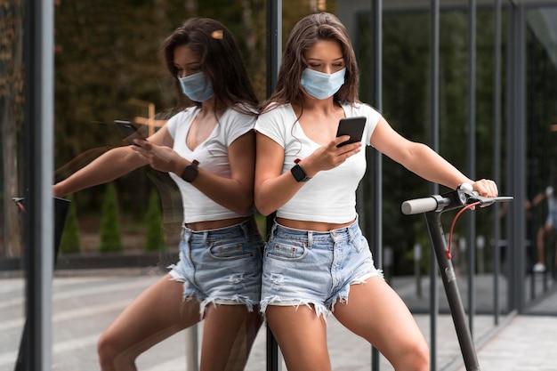 Frau mit medizinischer maske, die smartphone neben elektroroller prüft