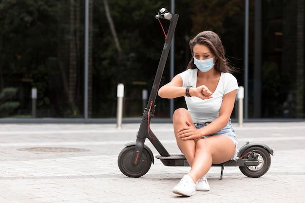 Frau mit medizinischer maske, die smartwatch beim sitzen auf elektroroller prüft