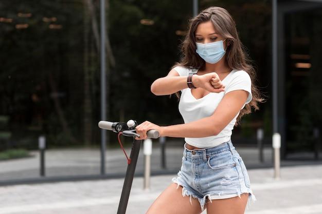 Frau mit medizinischer maske, die smartwatch überprüft, während auf elektroroller