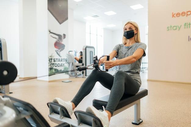 Frau mit medizinischer maske, die während der pandemie im fitnessstudio trainiert