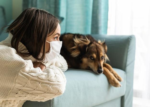 Frau mit medizinischer maske, die während der pandemie neben ihrem hund zu hause sitzt