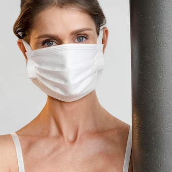 Frau mit medizinischer maske, die yogamatte hält