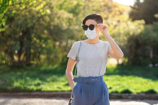 Frau mit medizinischer maske geht während des ausbruchs von covid 19 allein im park. schutz in der prävention des coronavirus. konzept der sozialen distanzierung.