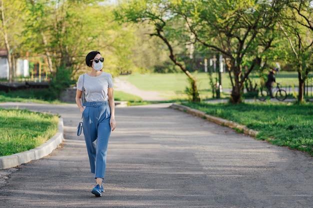 Frau mit medizinischer maske geht während des ausbruchs von covid 19 allein im park. schutz in der prävention des coronavirus. konzept der sozialen distanzierung. Premium Fotos