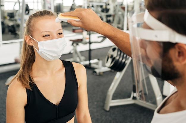 Frau mit medizinischer maske im fitnessstudio, die ihre temperatur vom mann mit gesichtsschutz überprüfen lässt