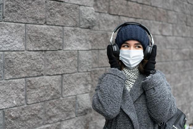 Frau mit medizinischer maske in der stadt, die musik auf kopfhörern hört