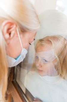 Frau mit medizinischer maske in quarantäne hinter fenster mit kleinem mädchen