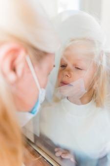 Frau mit medizinischer maske in quarantäne hinter fenster mit niedlichem mädchen