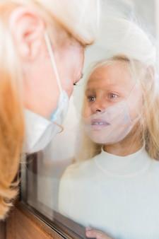 Frau mit medizinischer maske in quarantäne hinter fenster mit traurigem mädchen