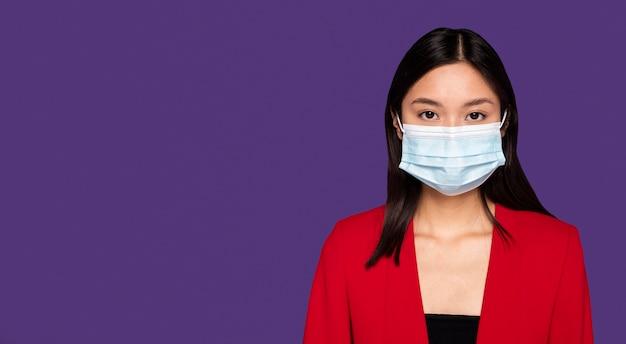 Frau mit medizinischer maske mit kopienraum