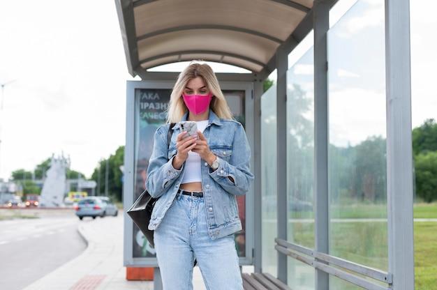 Frau mit medizinischer maske mit smartphone beim warten auf den öffentlichen bus