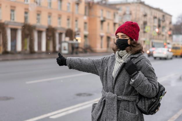 Frau mit medizinischer maske per anhalter in der stadt