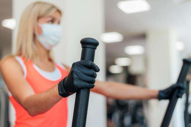 Frau mit medizinischer maske und handschuhen, die an der turnhalle arbeiten