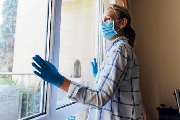 Frau mit medizinischer maske und handschuhen, die durch fenster während der quarantäne schauen