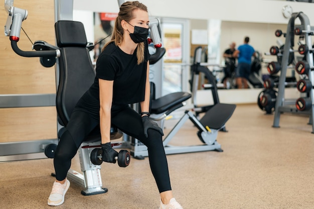 Frau mit medizinischer maske und handschuhen, die im fitnessstudio trainieren