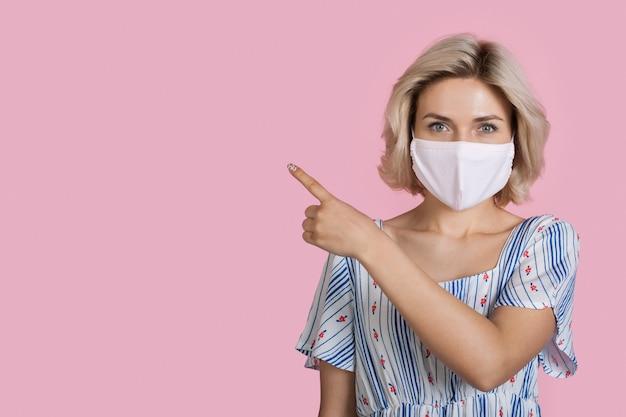 Frau mit medizinischer maske zeigt auf etwas