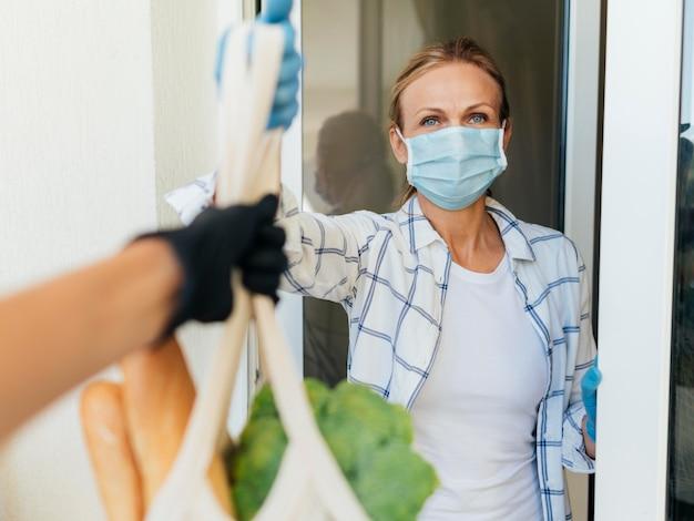 Frau mit medizinischer maske zu hause, die ihre lebensmittel in der selbstisolierung abholt