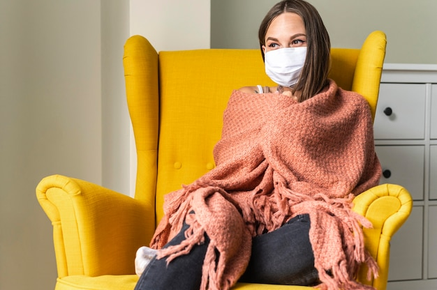 Frau mit medizinischer maske zu hause im sessel während der pandemie