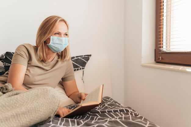 Frau mit medizinischer maskenlesung in quarantäne