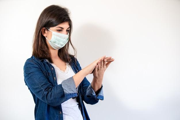 Frau mit medizinischer schutzmaske, die ihre hände reinigt.