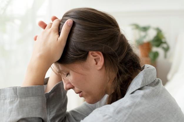 Frau mit migräne und kopfschmerzen