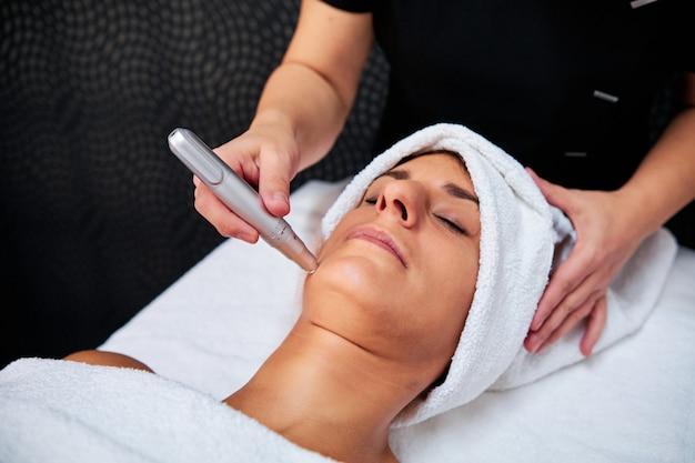 Frau mit mikronadelbehandlung im spa