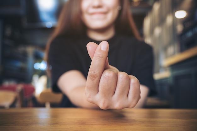 Frau mit mini-herz-handzeichen