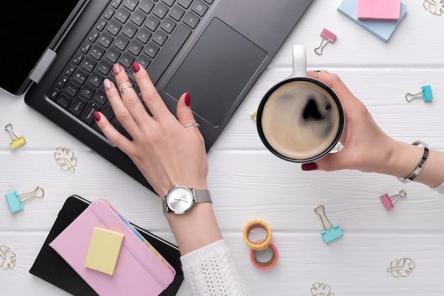 Frau mit minimalem rosa frühlingssommer-maniküreentwurf, der auf tastatur schreibt